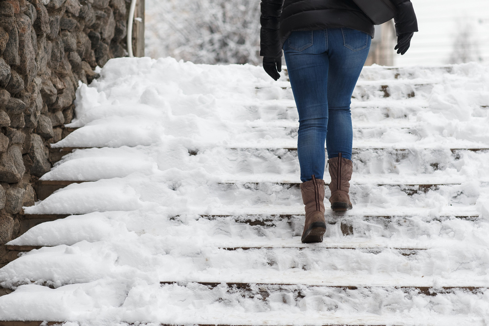 Woman walking on snowy steps.