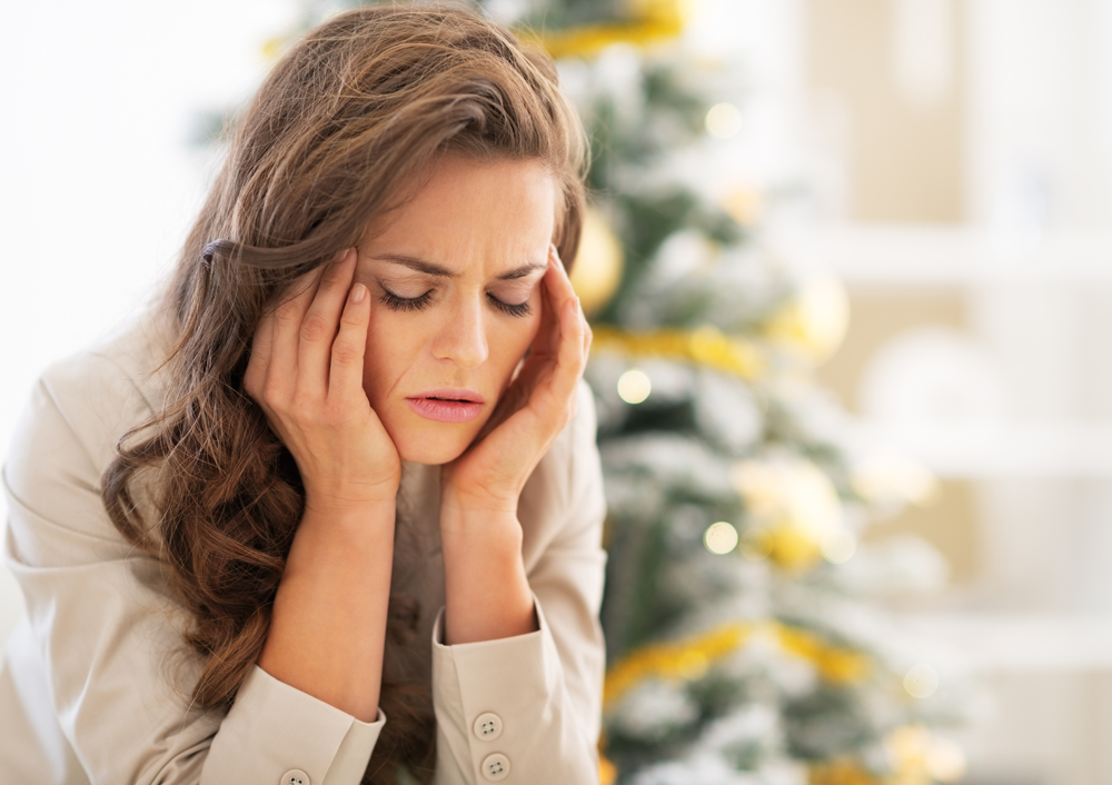 Woman with holiday stress fighting a headache.