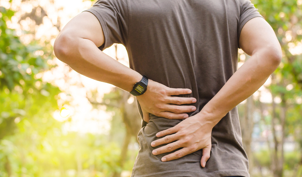 Man with lower back pain needs chiropractic care in Livonia.
