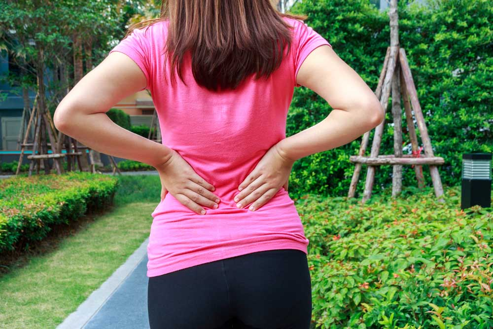 Woman suffering from back pain after yard work and gardening